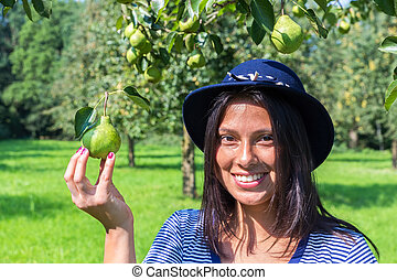 Woman wearing hat holding pear in orchard