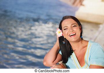 Woman wearing Hawaiian flower in hair enjoying the summer sun outdoors