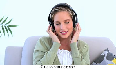 Woman wearing headphone and listening to music on couch