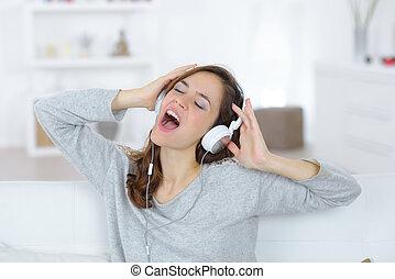 woman wearing headphones screaming with closed eyes