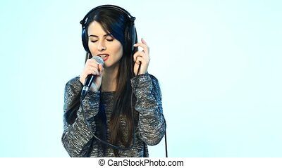 Woman wearing headphones with microphone singing