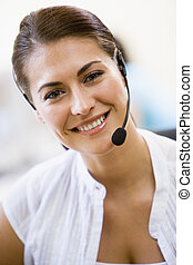 Woman wearing headset indoors smiling