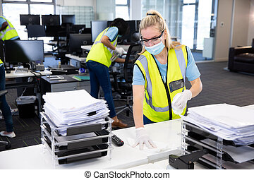 Caucasian woman and colleagues wearing hi vis vests, gloves, safety glasses and face masks sanitizing an office using disinfectant. Hygiene in workplace during Coronavirus Covid 19 pandemic.