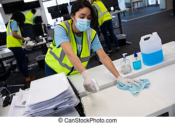 Mixed race woman and colleagues wearing hi vis vests, gloves and face masks sanitizing an office using disinfectant. Hygiene in workplace during Coronavirus Covid 19 pandemic.