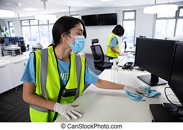 Mixed race woman and colleague wearing hi vis vests, gloves and face masks sanitizing an office using disinfectant. Hygiene in workplace during Coronavirus Covid 19 pandemic.