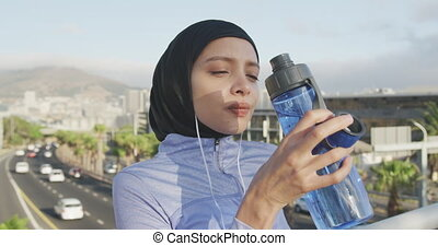 Woman wearing hijab drinking outside - Side view of a mixed ...