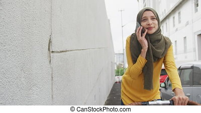 Woman wearing hijab having a phonecall on a bike - Front ...
