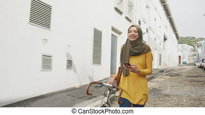 Front view of a mixed race woman wearing hijab in the city on a sunny day, walking the street and wheeling her bicycle, smiling and using smartphone in slow motion