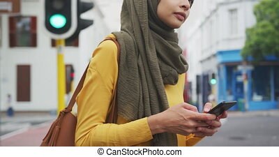 Woman wearing hijab holding her phone in the street - Side ...