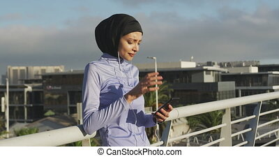 Woman wearing hijab listening music outside - Side view of a...