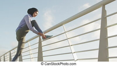 Woman wearing hijab listening music outside tying her ...