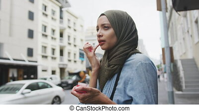 Woman wearing hijab putting lipstick in the street - Side ...