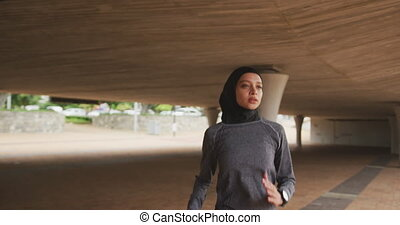 Woman wearing hijab running - Front view of a mixed race ...
