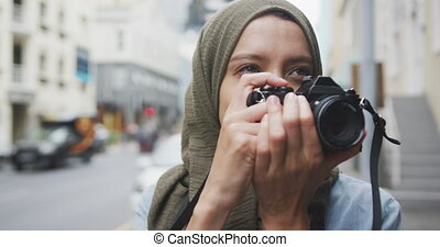 Woman wearing hijab taking photo in the street - Front view ...
