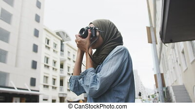 Woman wearing hijab taking photo in the street - Side view ...
