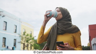 Side view of a mixed race woman wearing hijab in the city on a sunny day, walking the street and drinking takeaway coffee, using smartphone in slow motion