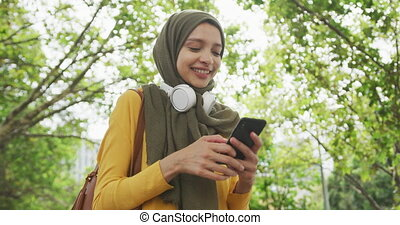Woman wearing hijab with wireless headphone and using her ...