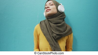 Woman wearing hijab with wireless headphone - Front view of ...