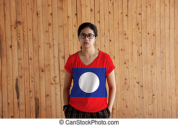 Woman wearing Laos flag color shirt and standing with two hands in pant pockets on the wooden wall background.