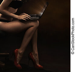 Woman wearing lingerie with laptop