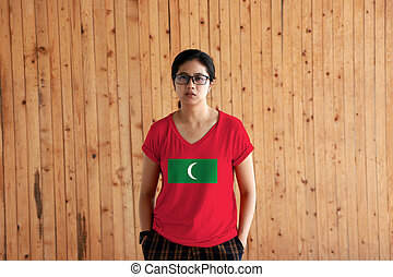 Woman wearing Maldives flag color shirt and standing with two hands in pant pockets on the wooden wall background.