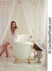 woman wearing man shirt sitting in bathroom
