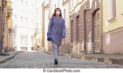 woman wearing mask and gloves walking in city - health, ...