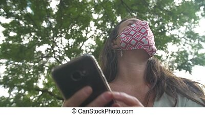 Selective focus of beautiful woman in city park feeling tensed wearing covid-19 protection safety mask while using smartphone and looking around