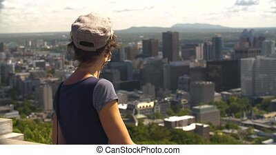 Young beautiful female tourist wearing cap and sling bag with covid-19 protective face mask standing on building top looking at cityscape horizon