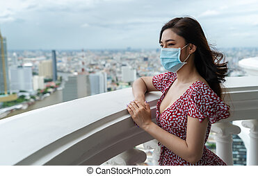 woman wearing medical mask for prevent to coronavirus(covid-19) and looking view of the city