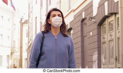 woman wearing medical mask walking in city - health, safety ...