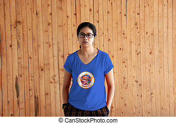 Woman wearing Minnesota flag color shirt and standing with two hands in pant pockets on the wooden wall background.
