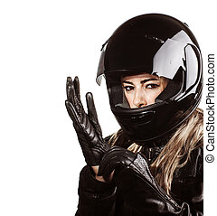 Closeup portrait of blond woman wearing motorsport outfit, isolated on white background, shiny black helmet and leather gloves, protective clothing