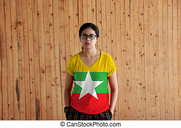 Woman wearing Myanmar flag color shirt and standing with two hands in pant pockets on the wooden wall background.