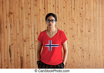 Woman wearing Norway flag color shirt and standing with two hands in pant pockets on the wooden wall background.