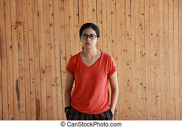 Woman wearing orange color of shirt and standing with two hands in pant pockets on wooden wall background.
