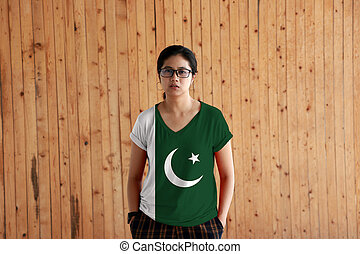 Woman wearing Pakistan flag color shirt and standing with two hands in pant pockets on the wooden wall background.