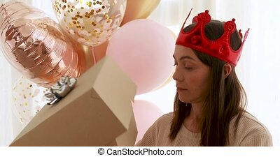 Woman wearing party hat getting shocked after opening present box