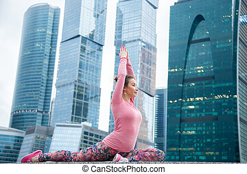 Woman wearing pink sportswear in One Legged King Pigeon pose...