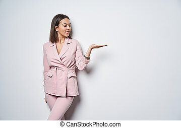 Woman wearing pink suit holding copy space on the palm