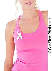 Woman wearing pink top and breast cancer ribbon on white...
