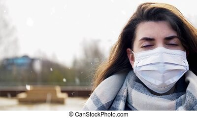 health, safety and pandemic concept - woman wearing protective medical mask outdoors over snow in winter