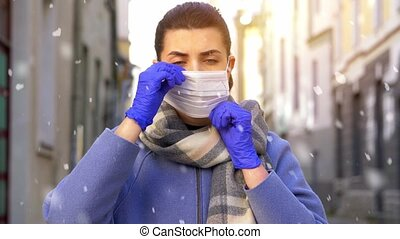 health, safety and pandemic concept - young woman wearing protective medical mask outdoors in winter