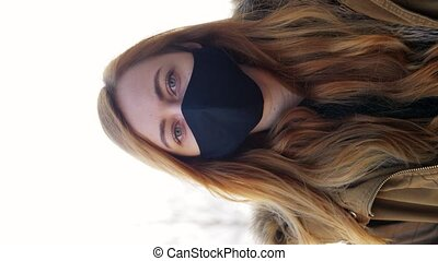 health, safety and pandemic concept - young woman wearing black face protective reusable barrier mask outdoors, vertical view orientation