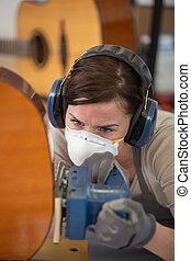 woman wearing protective workwear to polish a guitar