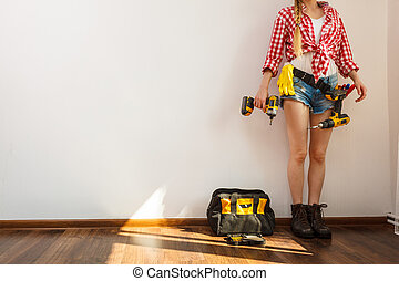 Woman wearing protective workwear using drill. Girl working at flat remodeling. Building, repair and renovation.