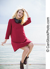 Woman wearing red dress and headphones