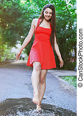 Woman wearing red dress jumping into a puddle after the rain