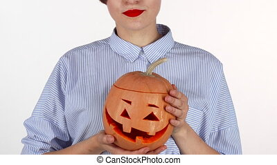 Woman wearing red lipstick holding up carved halloween...