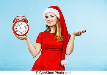 Woman wearing Santa Claus costume holding clock